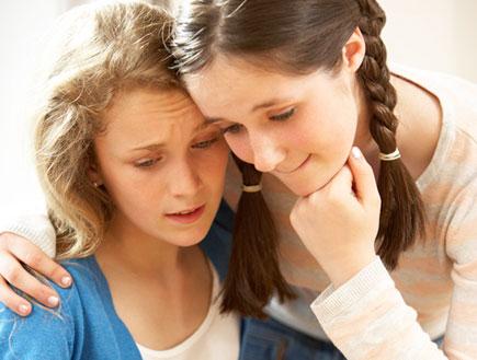 שתי נערות מחובקות מביטות בבדיקת הריון בדאגה (וידאו WMV: jupiter images)
