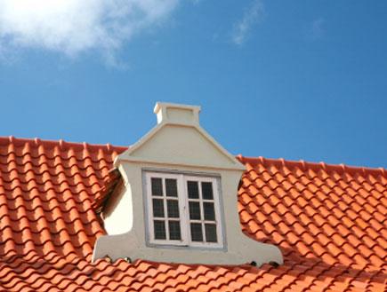 חלון לבן של עליית גג עם רעפים אדומים וברקע שמיים (צילום: istockphoto)