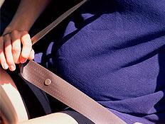 בטן הריונית בסגול עם חגורת בטיחות באוטו (צילום: jupiter images)