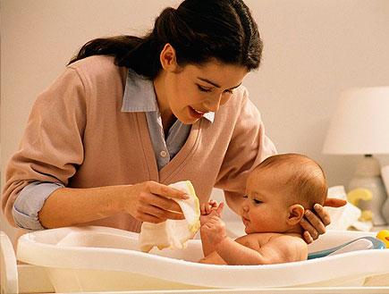אישה מקלחת תינוק ומחזיקה את ראשו (צילום: istockphoto)