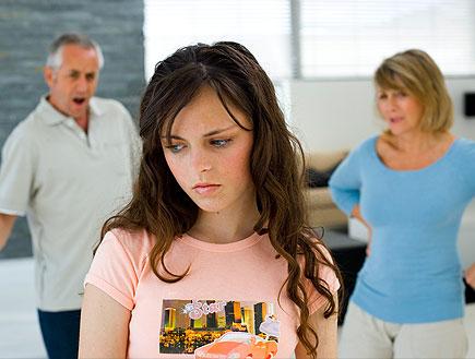 נערה עצובה בורוד וברקע הוריה עומדים כועסים (צילום: jupiter images)