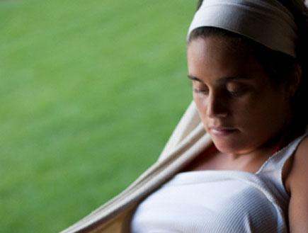 בחורה בהריון בערסל על דשא מביטה על הבטן
