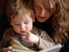 בחורה מקריאה סיפור לפעוט שיושב עליה (צילום: blackjake, Istock)