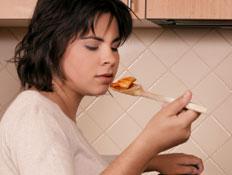 אישה בהריון טועמת אוכל שמבשלת בסיר