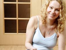 אישה בהריון יושבת על רצפת פרקט ומחזיקה קערת קורנפלקס (צילום: istockphoto)