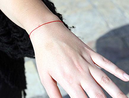 יד מושטת,עונדת צמיד אדום של קבלה (צילום: עודד קרני)
