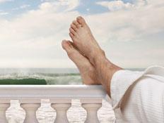 רגליים על מעקה מרפסת לבנה