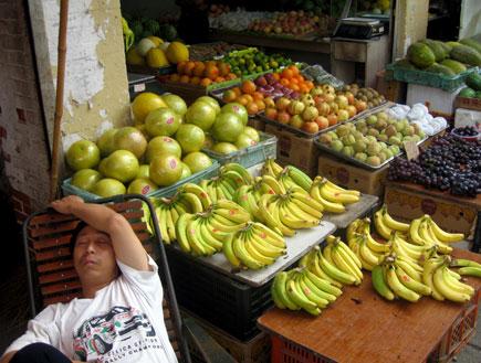 תאילנדי יושב ליד דוכן פירות