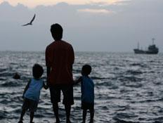 יום כיף: אב ושני ילדים על החוף בשקיעה (צילום: Reuters)