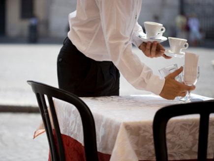 מלצר מפנה שולחן (צילום: istockphoto)