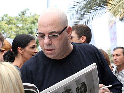 רון קופמן קורא עיתון (צילום: עודד קרני)