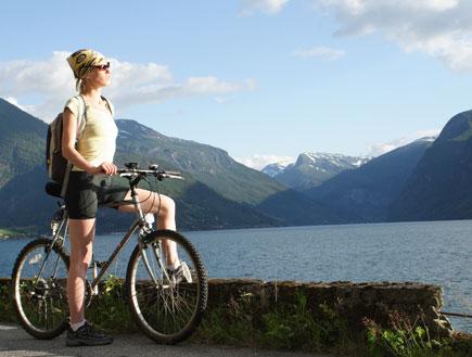 בחורה על אופניים ליד אגם (צילום: Shutterstock)