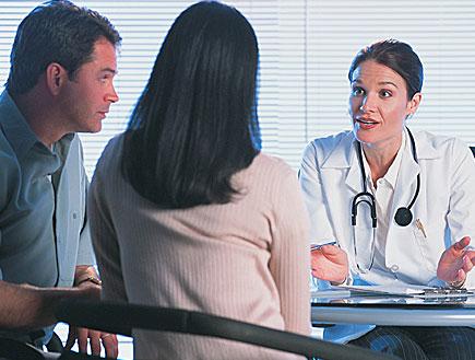 גבר ואישה יושבים בשולחן ומקשיבים לרופאה בחלוק (צילום: jupiter images)