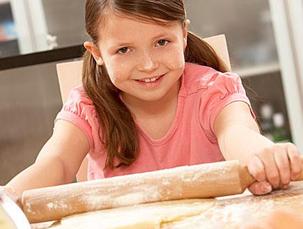 ילדה בורוד לשה בצק עם מערוך ומחייכת (צילום: jupiter images)
