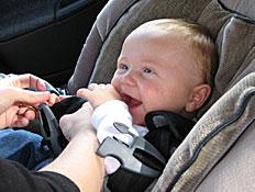 ידיים חוגרות בכיסא ברכב תינוק מחייך עם אצבע בפה (צילום: istockphoto)