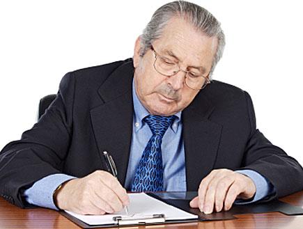 איש מבוגר יושב בחליפה ועניבה וכותב בעט על דף (צילום: Gelpi, Istock)