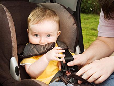 תינוק בצהוב נחגר לכיסא בטיחות ומלקק את החגורה (צילום: RichHobson, Istock)