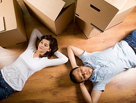 זוג צעיר שוכב על הגב על פרקט ומסביבם ארגזי קרטון (צילום: istockphoto)