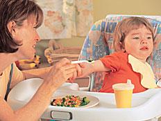אמא מנסה להאכיל בירקות את ילד סרבן בכיסא