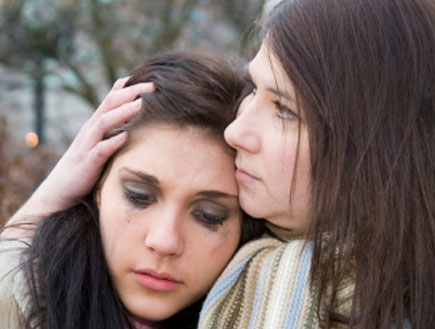 אישה מחבקת ומלטפת נערה בוכה עם איפור מרוח (צילום: quavondo, Istock)