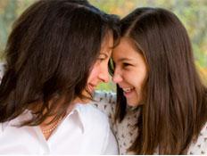 אישה וילדה צוחקות ומצמידות ראש לראש