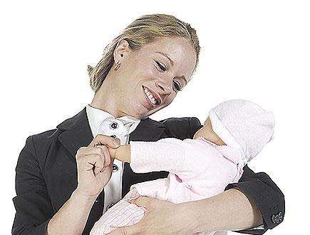 אישה בחליפה מחזיקה בובת תינוק ומחייכת (צילום: jupiter images)