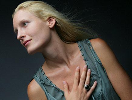 בחורה בלונדינית בירוק עם יד על החזה מביטה הצידה (צילום: jupiter images)