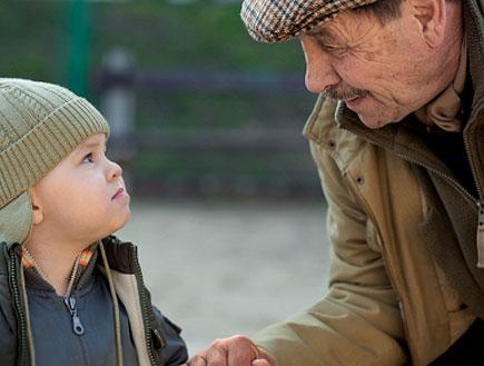 זקן וילד בכובע מחזיקים ידיים ברחוב ומסתכלים זה על זה (צילום: jupiter images)