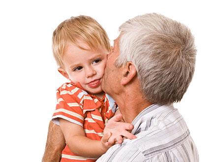 איש מבוגר בלבן מחזיק ומנשק ילד בלונדיני בפסים כתומים (צילום: jupiter images)