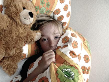 ילד בלונדיני במיטה עם דובי לידו מתחבא מתחת לשמיכה (צילום: istockphoto)