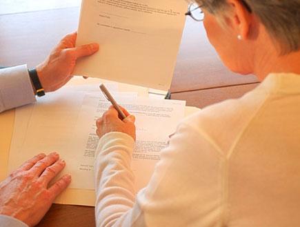 אישה מבוגרת במשקפיים מהגב חותמת על נייר שידי גבר מחזיקות (צילום: jupiter images)