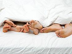 ארבעה זוגות רגליים מבצבצות משמיכת פוך לבנה