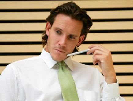 גבר בעניבה ירוקה עם עט יושב לשולחן וחושב (צילום: jupiter images)
