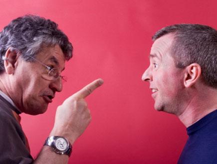 שני גברים משוחחים על רקע ורוד אחד במשקפיים מפנה אצבע לשני (צילום: Randolph Pamphrey, Istock)
