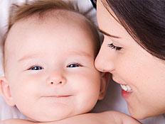 קלוז אפ של אישה מצמידה פניה לתינוק מחייך