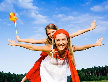 בחורה בלבן מרימה ילדה בכתום פורשות ידיים לצדדים על דשא (צילום: Izabela Habur, Istock)