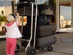 עגלת נשיאת מזוודות וילדה קטנה