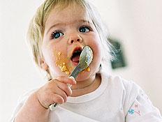 תינוקת אוכלת ומרוחה במחית ויושבת על הצלחת (צילום: jupiter images)