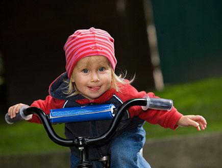 ילדה בכובע ורוד על אופניים מוציאה לשון (צילום: istockphoto)