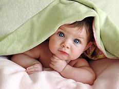 תינוק יפה וערום מציץ מתחת לשמיכה ירוקה על מיטה (צילום: ekinsdesigns, Istock)