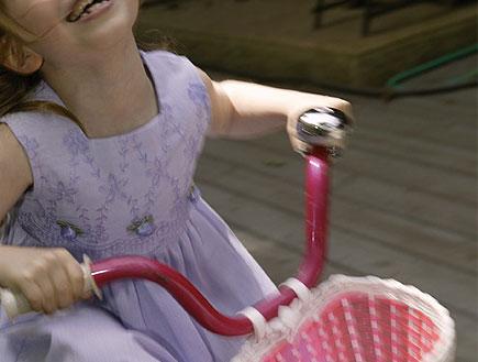 ילדה שמחה בשמלה סגולה על אופניים ורודות עם סל (צילום: jupiter images)