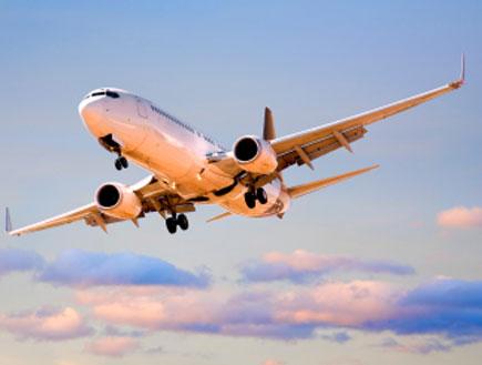 מטוס בתעופה בזמן זריחה