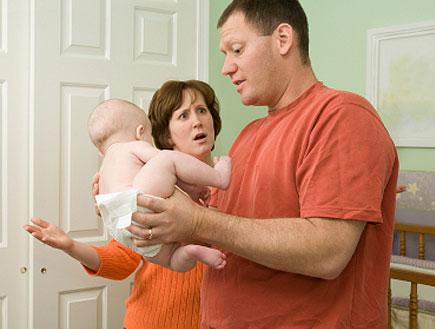 גבר מחזיק תינוק ואישה זעופה בכתום לידו (צילום: Nancy Louie, Istock)