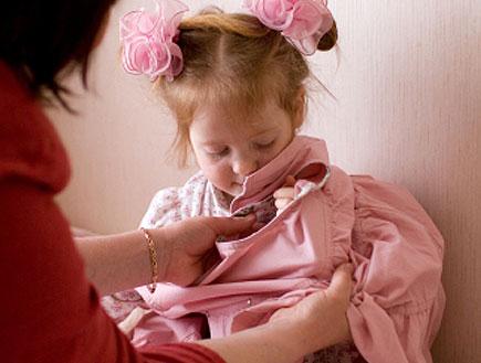 אישה מלבישה ילדה בבגד ורוד על המיטה (צילום: istockphoto)