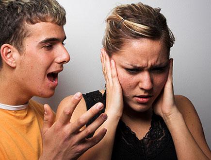 בחור בכתום מדבר אל בחורה שסותמת אוזניה (צילום: Miodrag Gajic, Istock)
