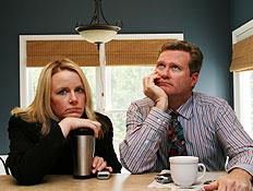 גבר ואישה יושבים בשולחן עם כוסות וחושבים
