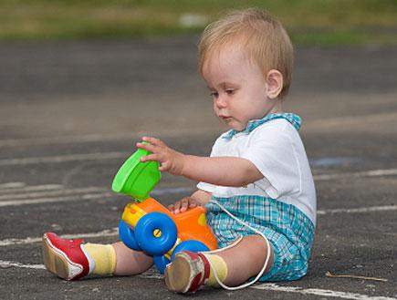 פעוט יושב על הרצפה ומשחק במכונית צעצוע (צילום: Sergey Kolodkin, Istock)