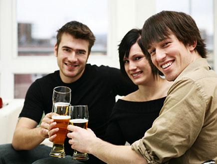 שני בחורים מרימים לחיים עם כוס בירה עם בחורה (צילום: istockphoto)