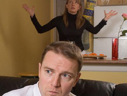 גבר כועס על ספה ומאחוריו אישה מתוסכלת בשחור (צילום: istockphoto)
