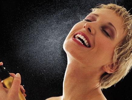 אישה מתיזה בושם (צילום: jupiter images)